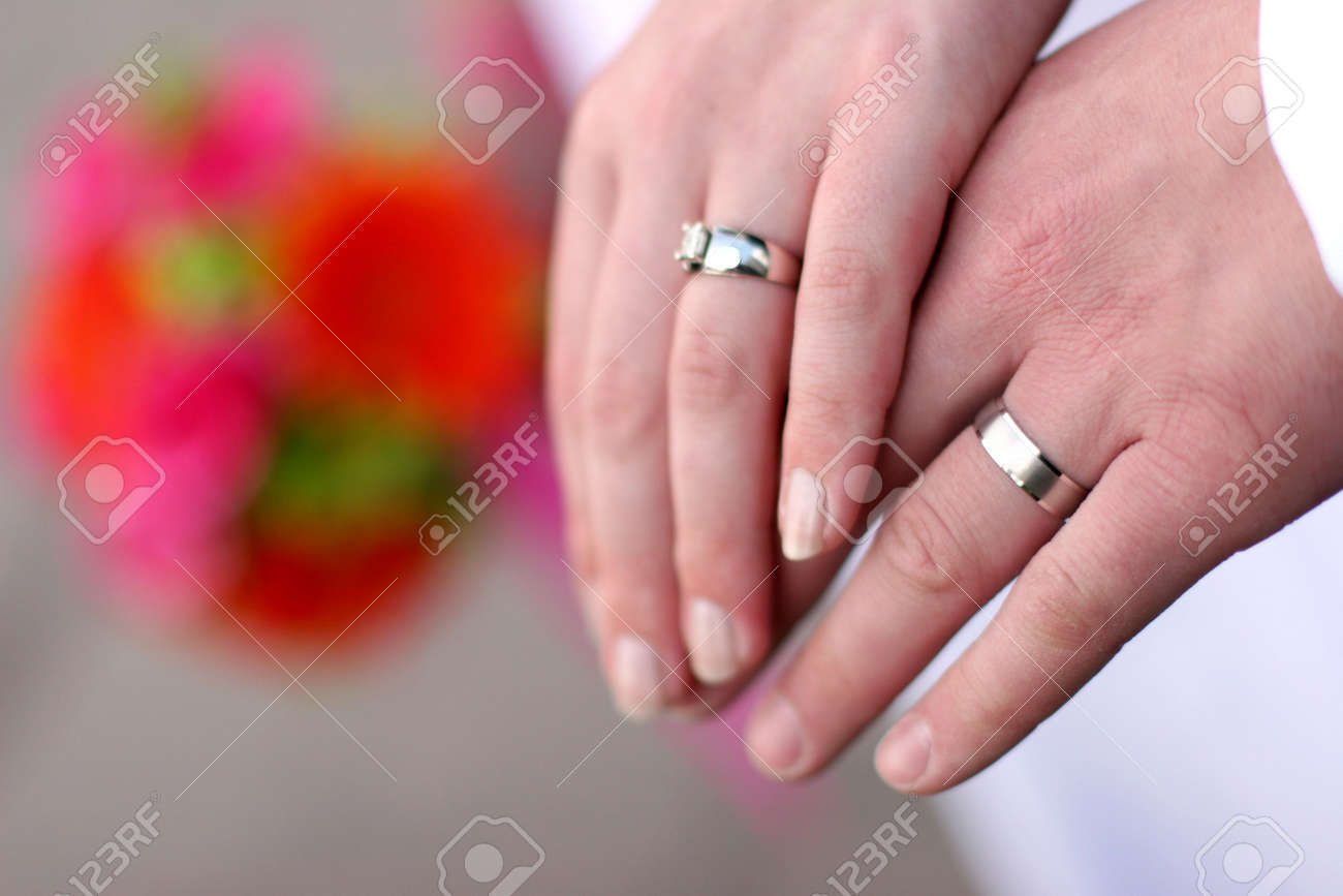Wedding Engagement With Two Hands, Their Rings, And Flowers In ...