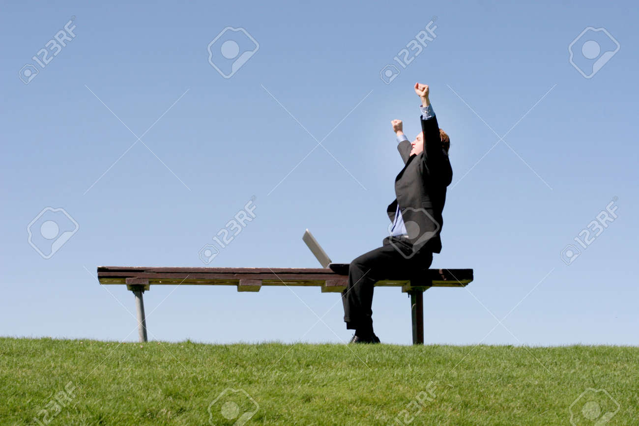 Businessman is waving his hands in celebration as he sits on a park bench, next to his laptop Stock Photo - 456788