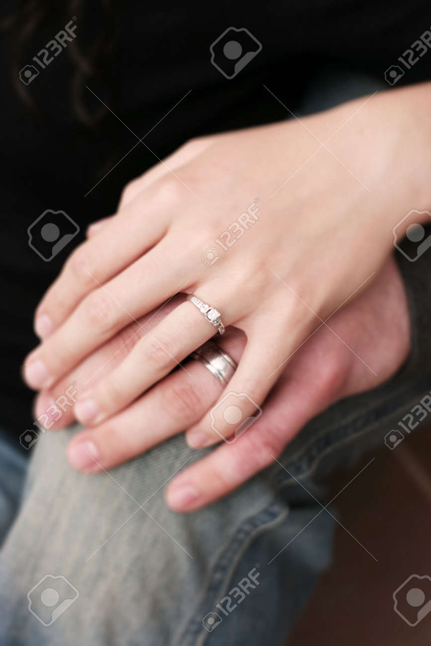 Couples\' Hands Are One On Top Of The Other With Engagement Rings ...