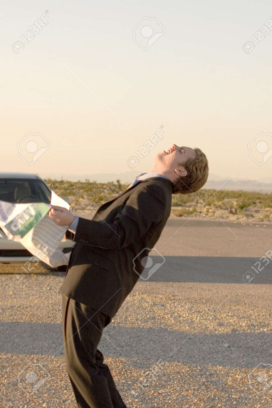Businessman is in a frustrated pose as he holds his map in his hands outside his parked car in the middle of the desert Stock Photo - 2543931