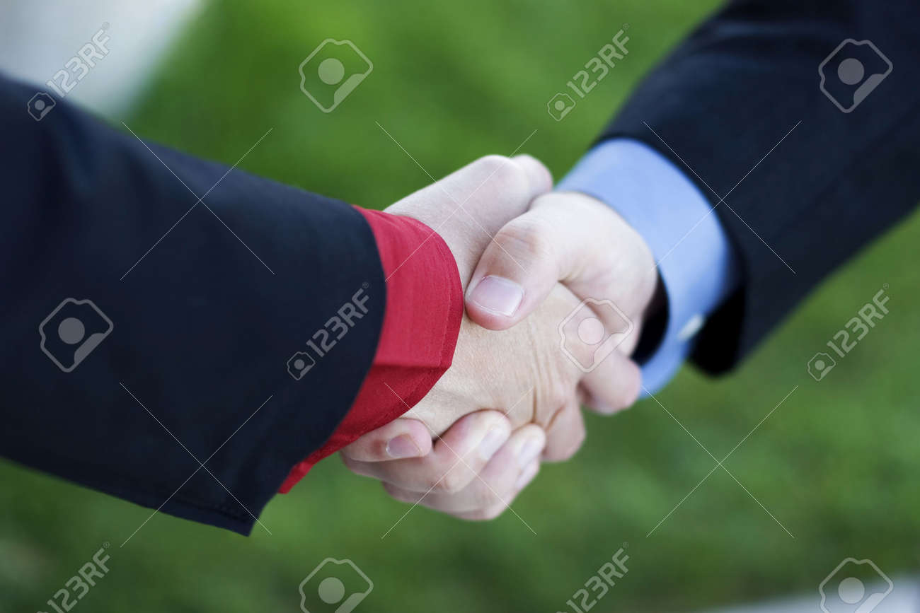 Two Businessmen seal their deal with a Handshake with green grass in the background Stock Photo - 2748485