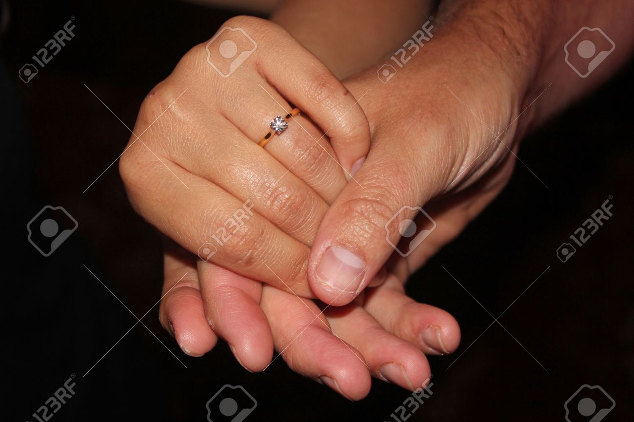 Man S Hand Holding A Women S Hand Showing Off An Engagement Ring