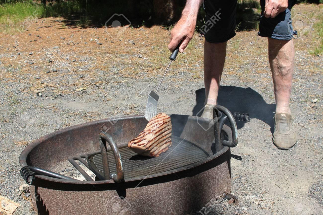Man Kocht Ein Grosses Stuck Steak Auf Dem Grill Uber Eine Feuerstelle Symbolisiert Bbq Kochen Manner Tun Die Kuche Und Das Kochen Im Freien Im Sommer Lizenzfreie Fotos Bilder Und Stock Fotografie