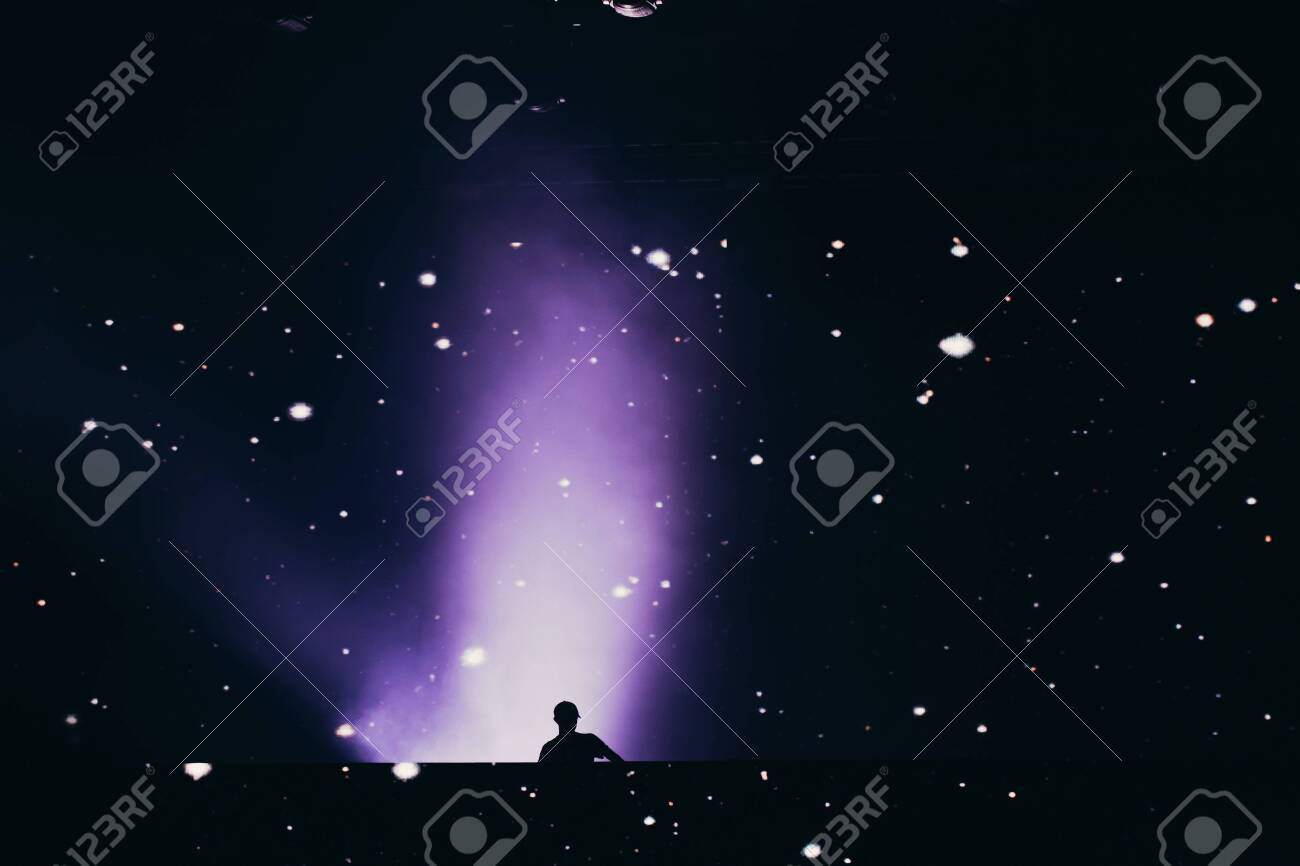 Stage lights and crowd of audience with hands raised at a music festival. Fans enjoying the party vibes. - 142175101
