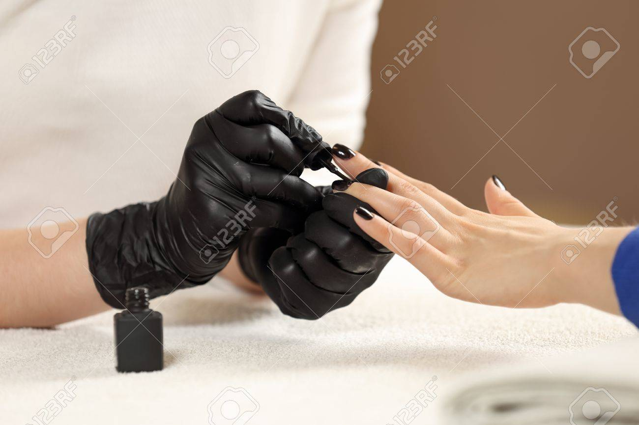 Black gloves with nails - Closeup Picture Manicurist Paints Client Nails In Spa Beauty Salon Manicure Master In Black Gloves