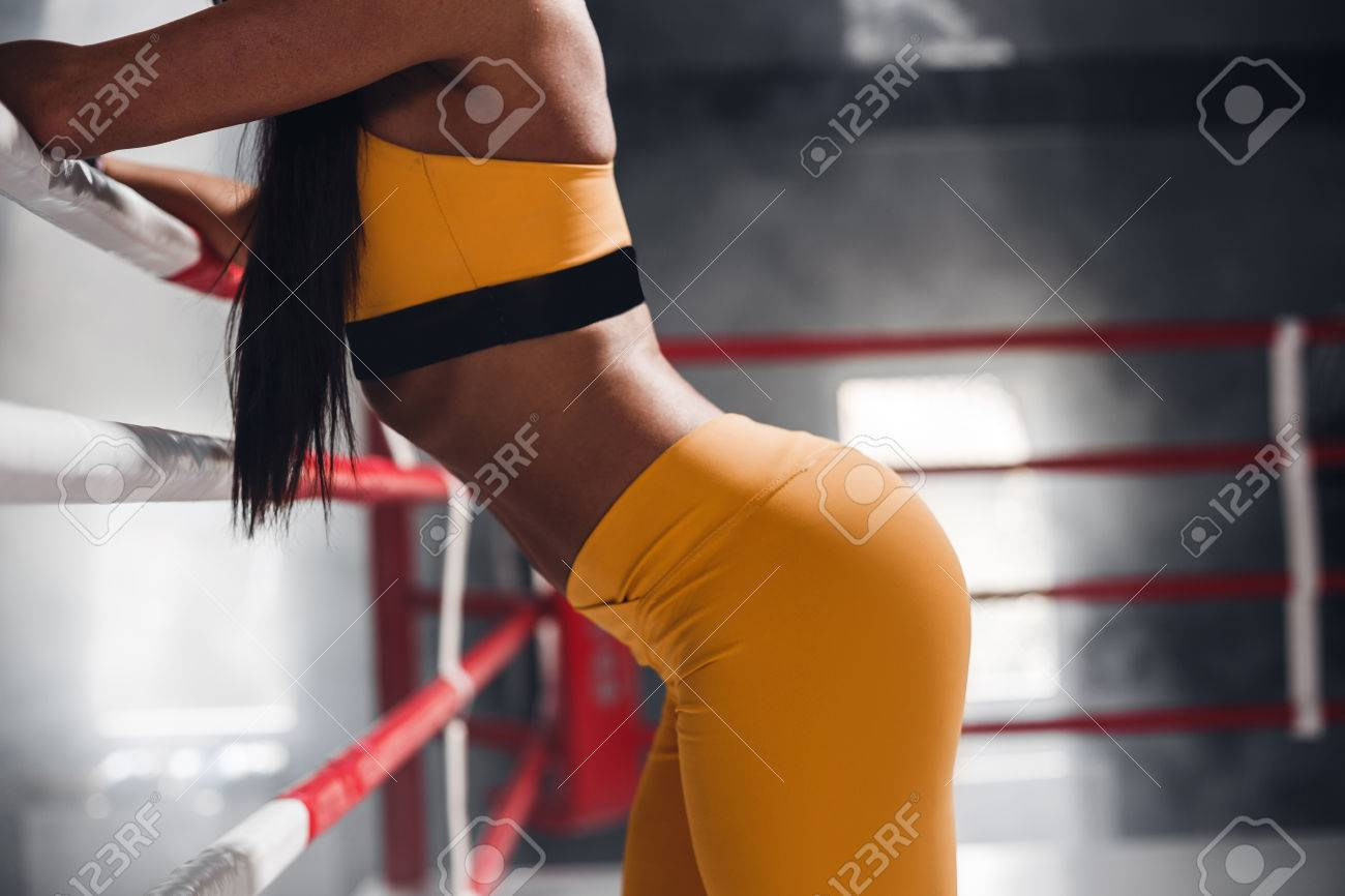 closeup of a young womans body against the backdrop of a boxing
