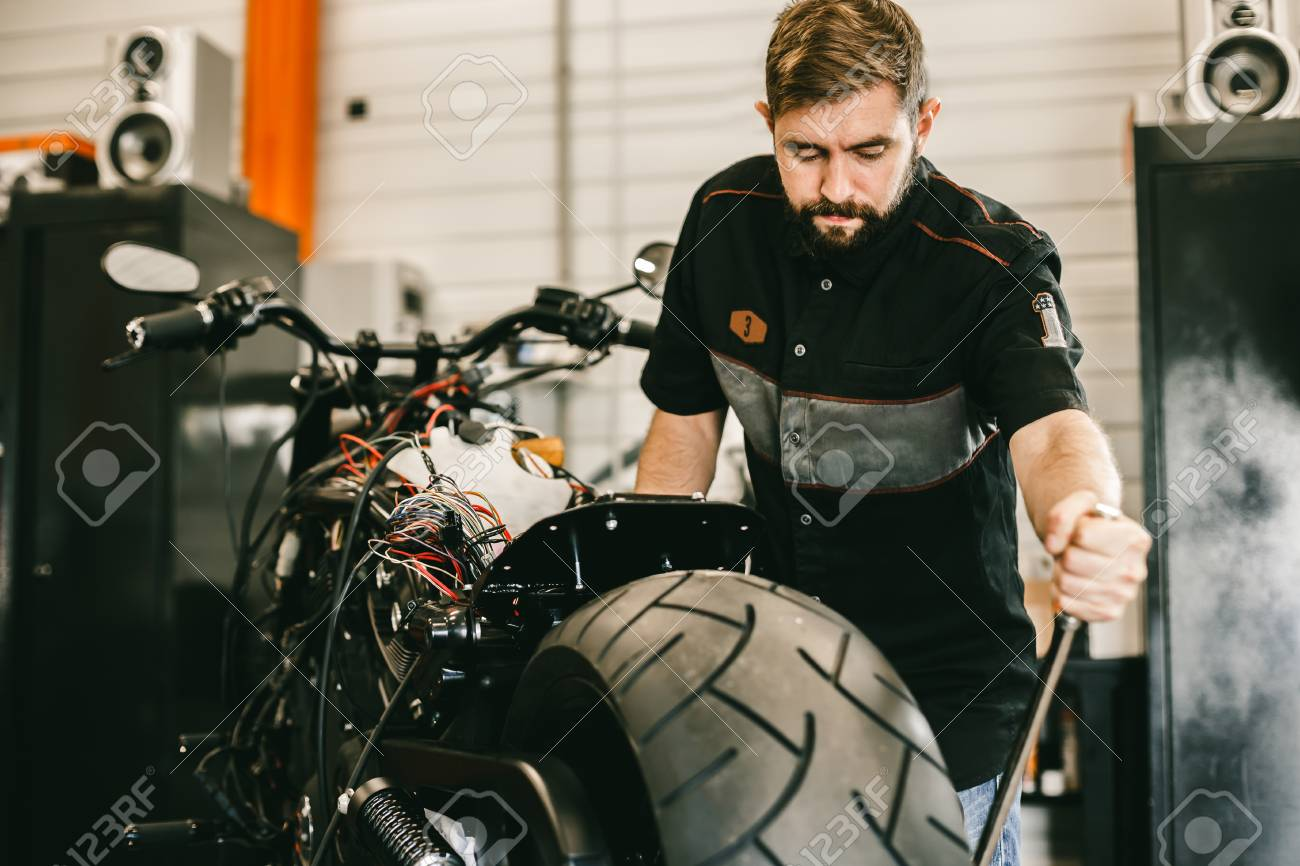 handsome mechanic removing motorcycle wheel with special tools professional motorcycle mechanic working in bike repair