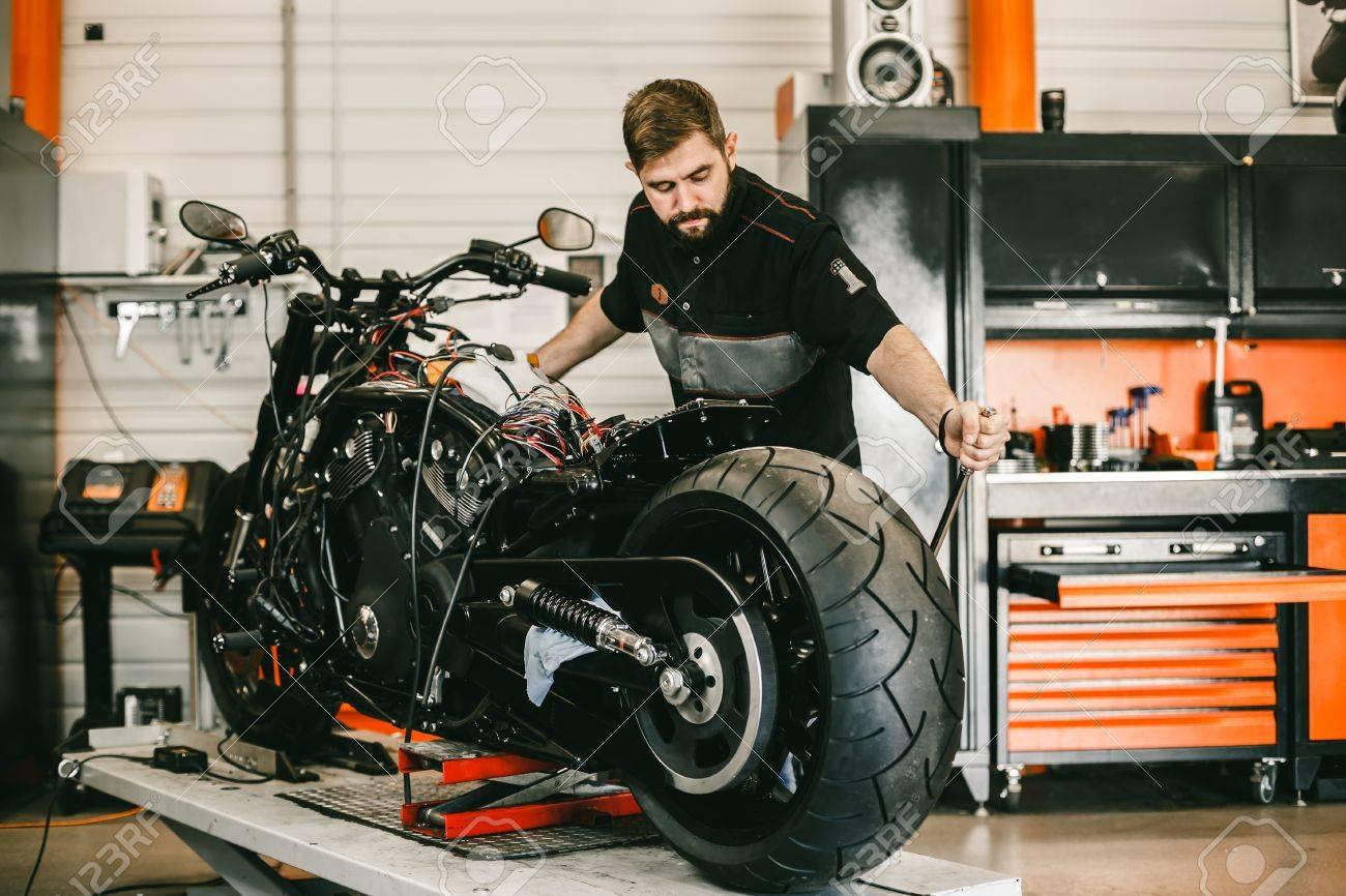 mechanician changing motorcycle wheel in bike repair shop professional motorcycle mechanic working in bike repair