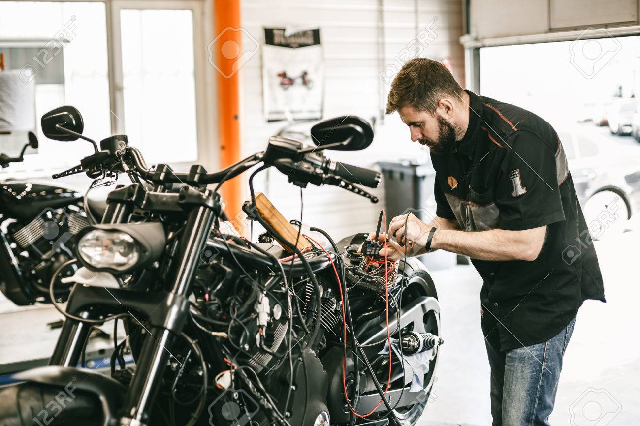 professional motorcycle mechanic working in bike repair service mechanic checking a bike battery level with