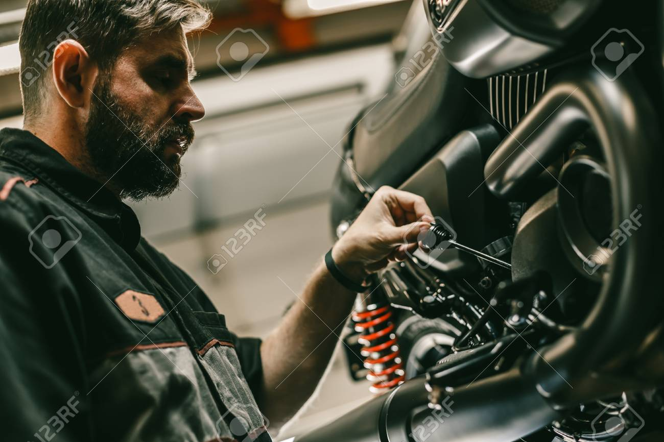 close up bottom view of the handsome motorcycle mechanic checks the oil level in the motorcycle