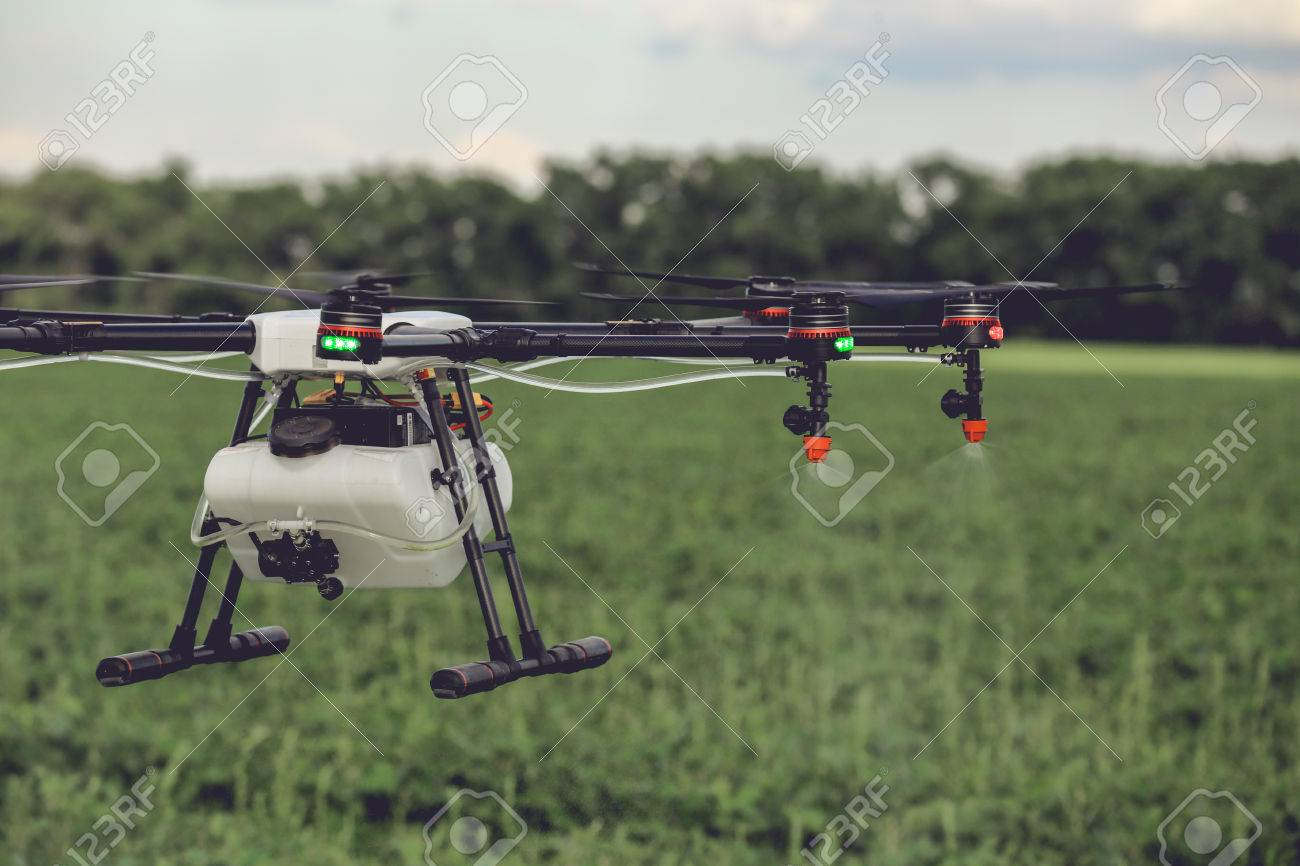 Closeup view of agriculture drone spraying water fertilizer on