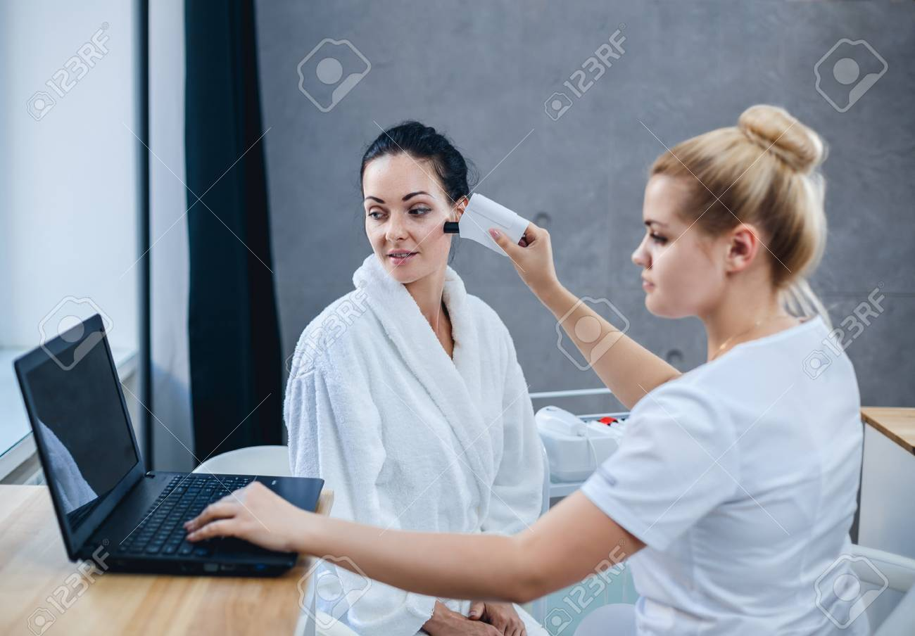 Female doctor and patient during examination of facial skin. The results of the skin condition are shown on the laptop. - 87551437