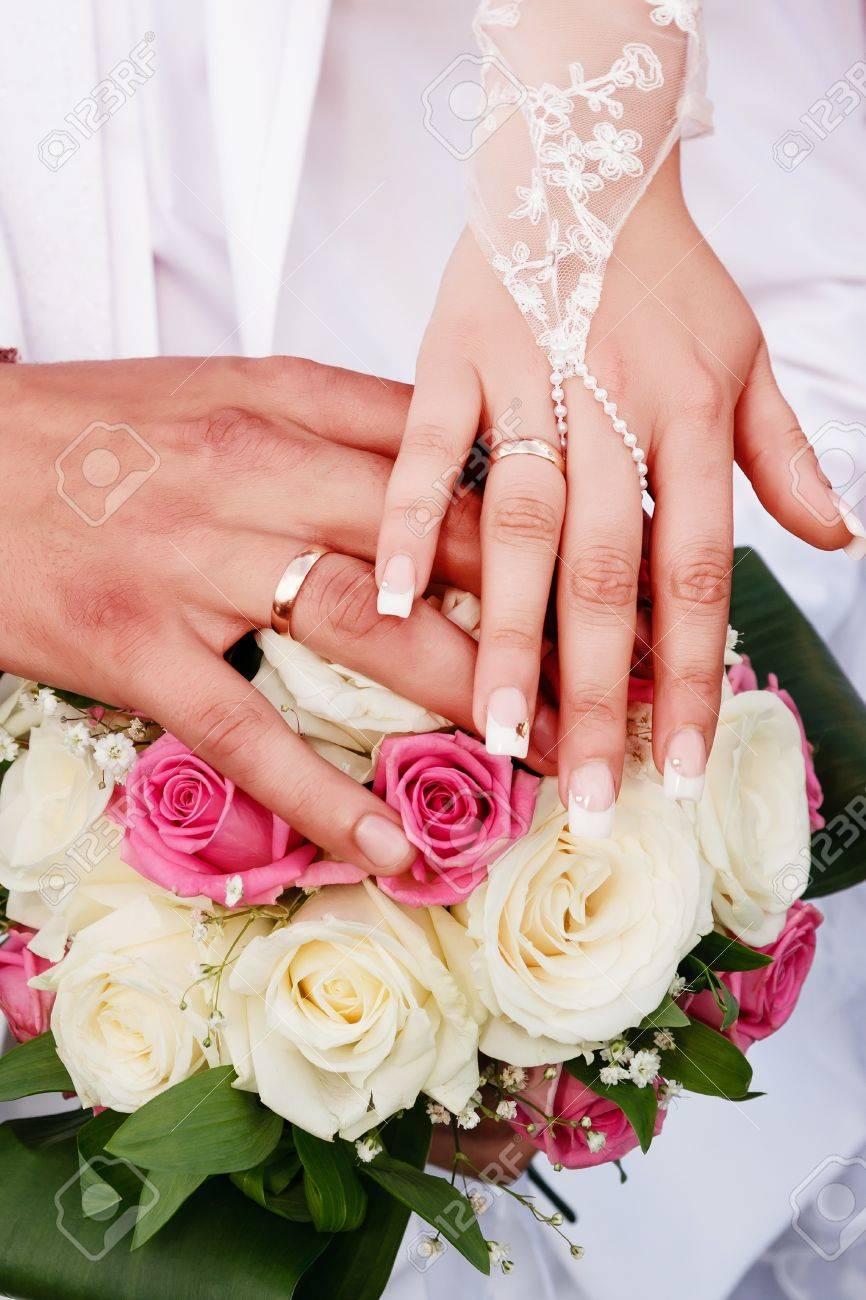 Hands honeymooners on the wedding bouquet of roses, wedding rings..
