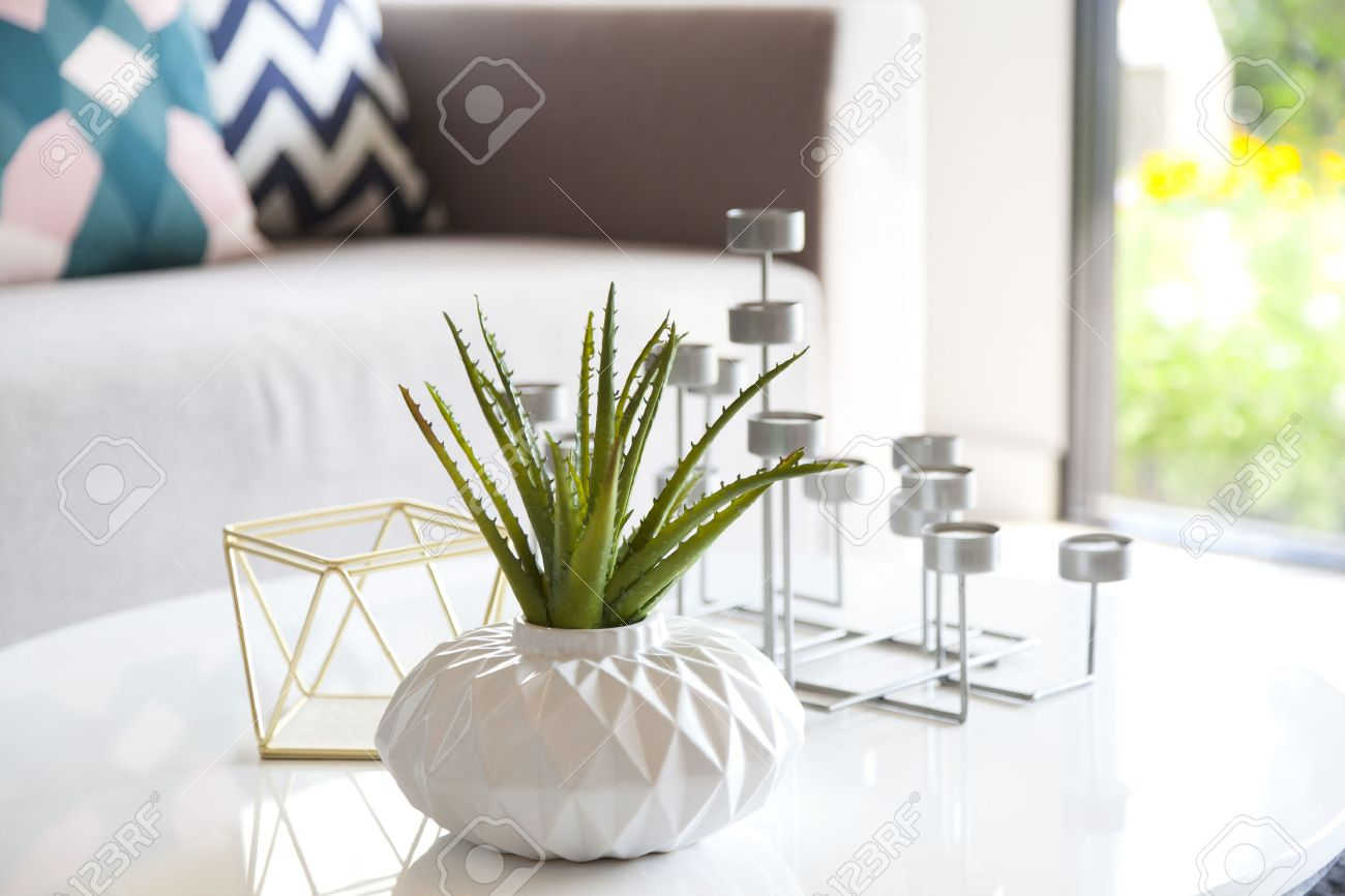 green plant in a vase and candle stand in living room stock photo