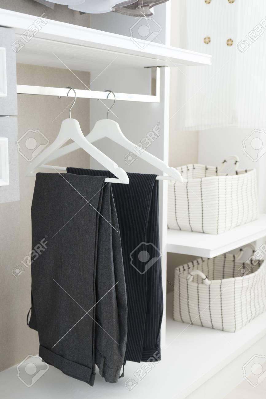 edadb37368 modern closet with row of pants hanging in white wardrobe Stock Photo -  96209644