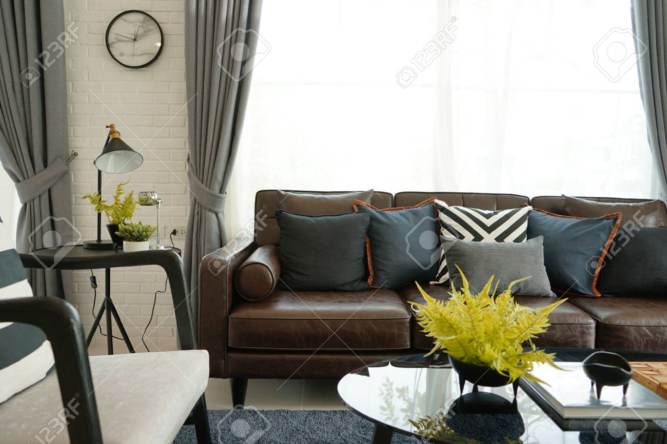 Modern decorative pillow on brown leather sofa in living room