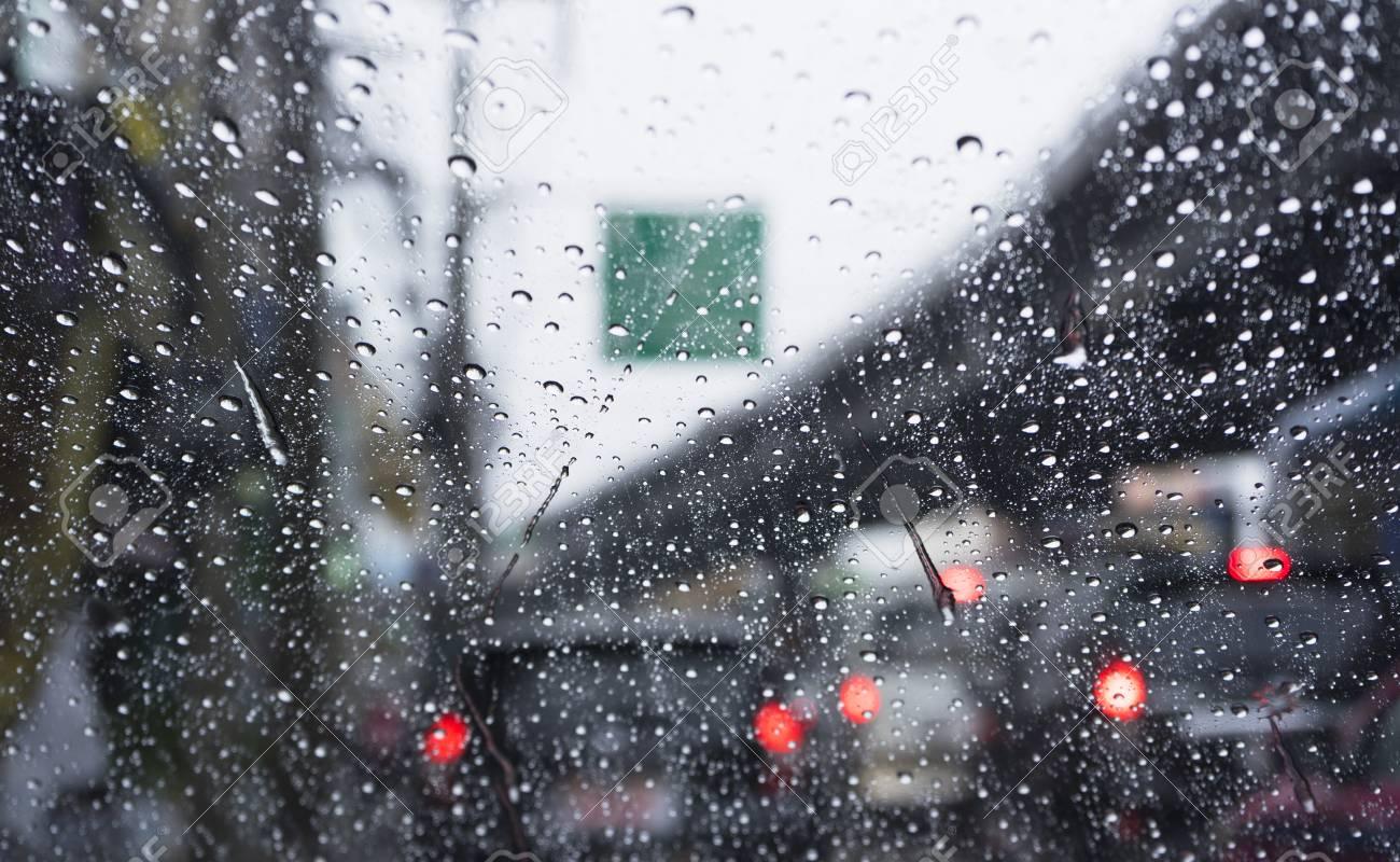 Road view through car window  Rain drops on car window, blurred