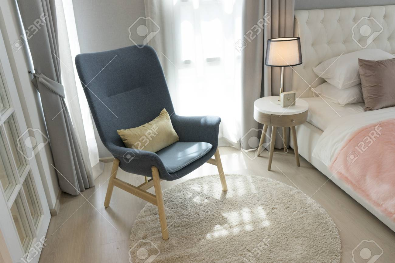 photo blue scandinavian armchair sitting in bedroom with side table and carpet
