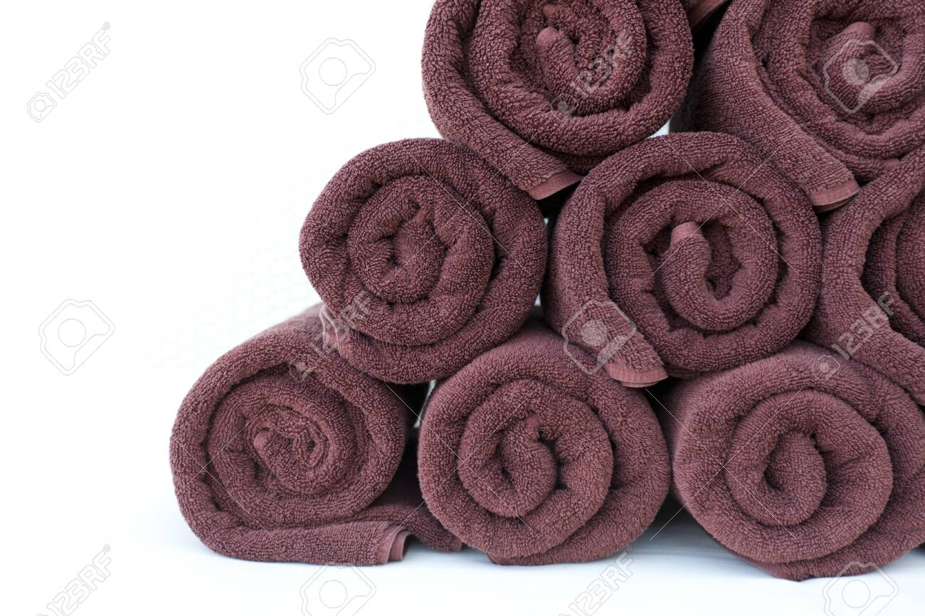 Stack roll of bath towels on table at swimming pool.