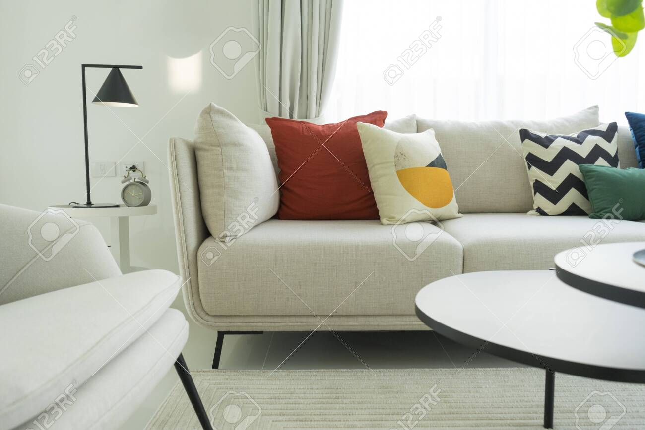 Large white sofa with colorful cushions in a spacious living..