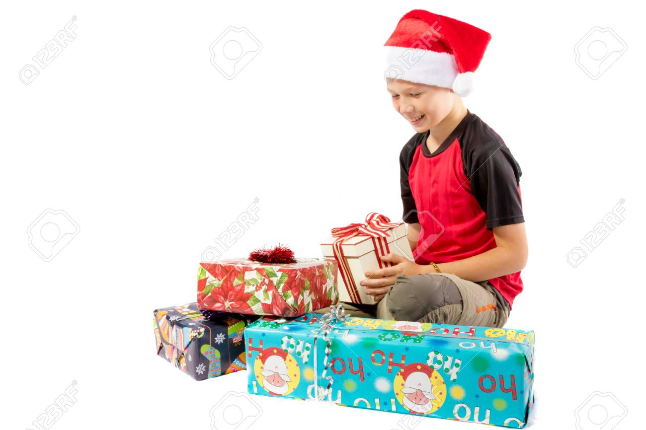 Happy Pre Teen Boy With A Pile Of Christmas Gifts Isolated On White Background Stock