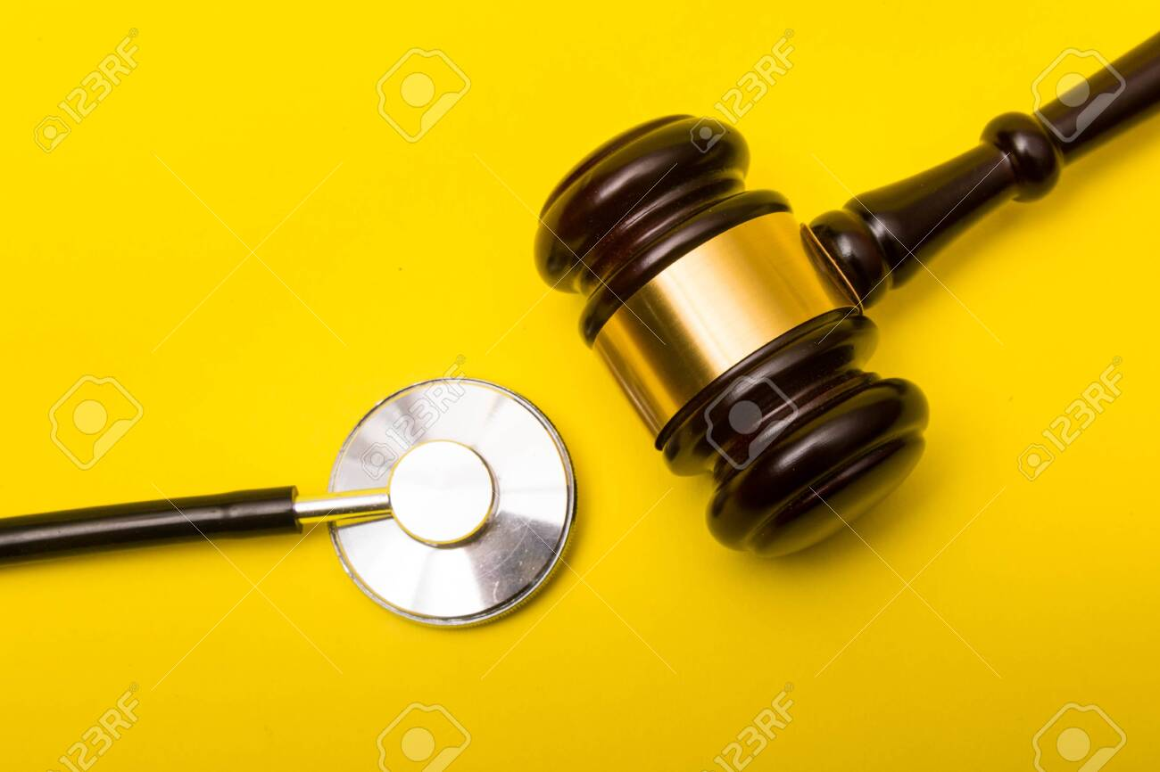 Medical malpractice lawsuit concept showing a gavel and a stethoscope on a yellow background - 134226278