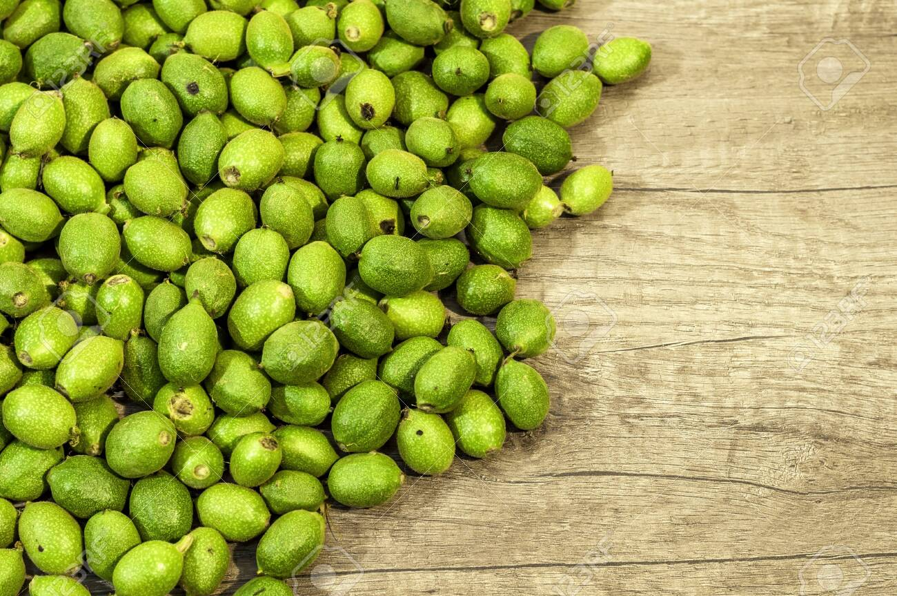 A lot green young walnuts in husks on wooden table - 120493125