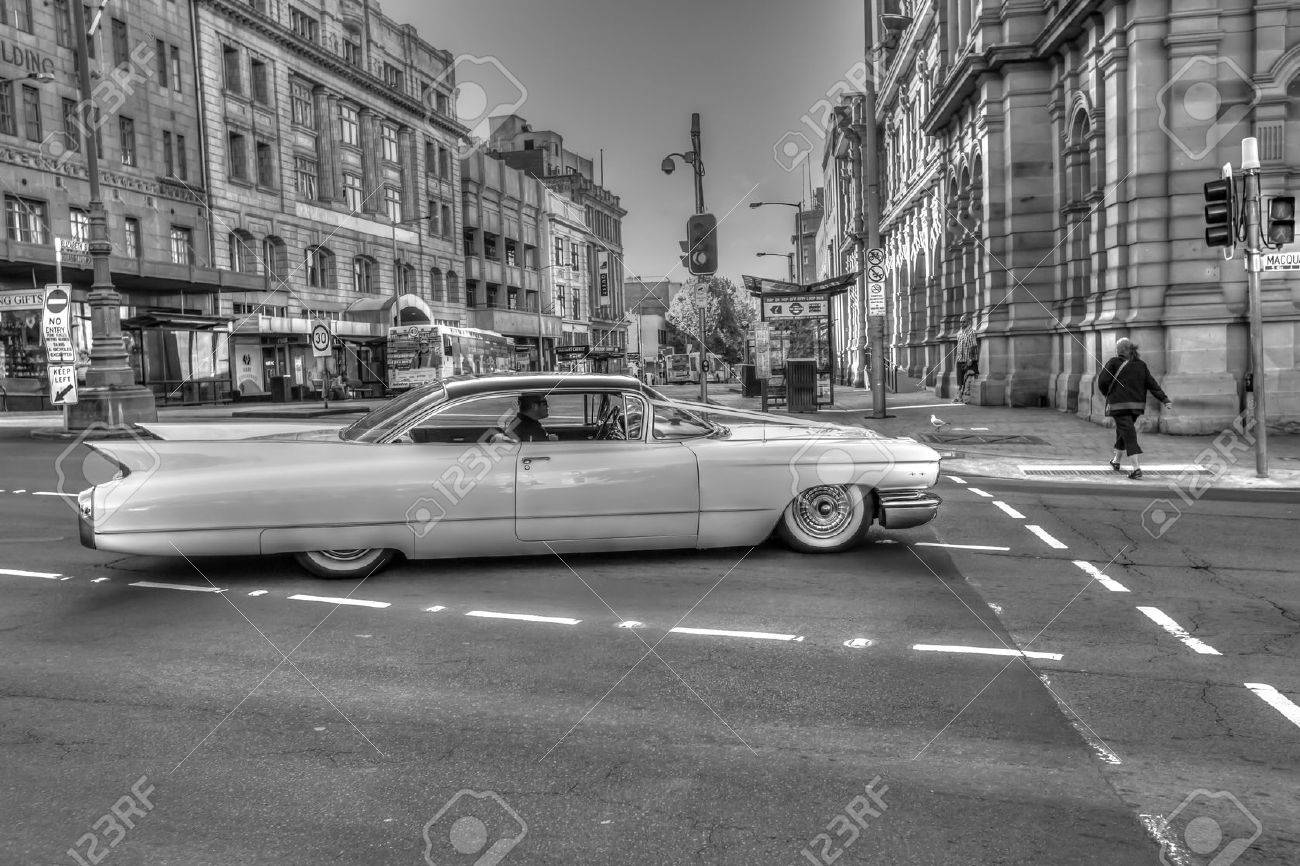 Hobart, Tasmania, Australia - January 16, 2015: Urban scenery in town as retro-style, black and white. A luxury vintage Cadillac running through streets of historic town. Stock Photo - 42364849