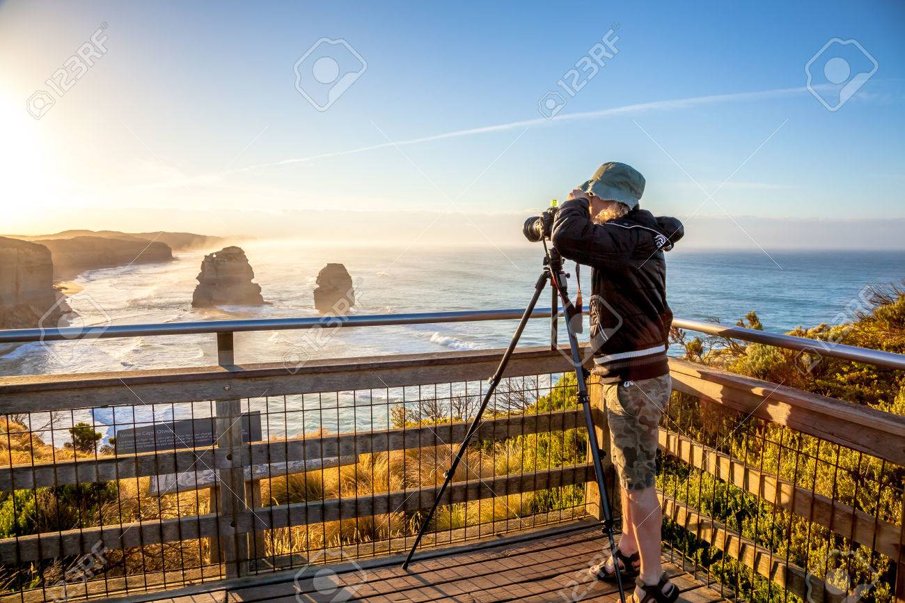 Nature australian photographer taking pictures at sunset With His tripod  and wide angle chamber to the