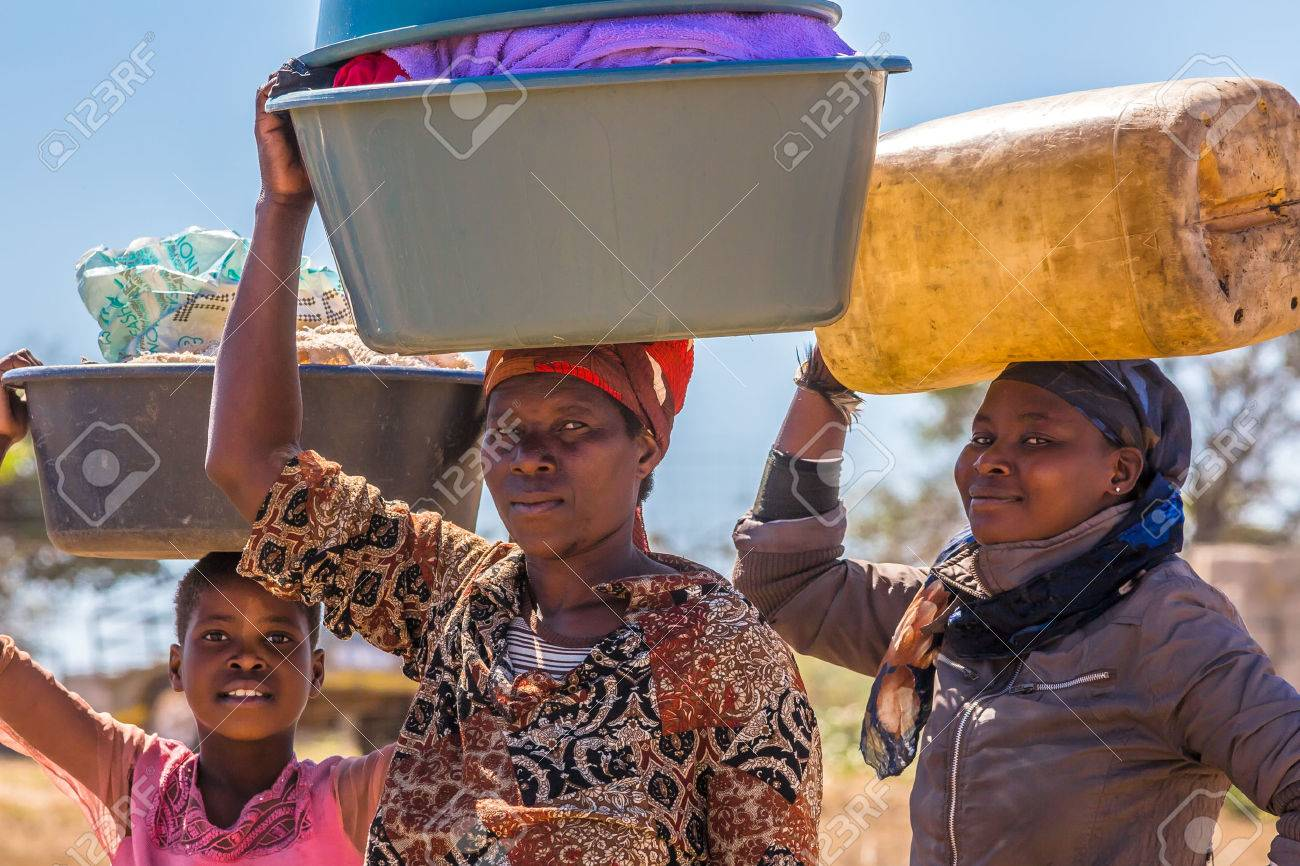 UMkhuze Game Reserve, South Africa - August 24, 2014: African women go to wash their clothes in the river, carrying basins on their heads Stock Photo - 45848979