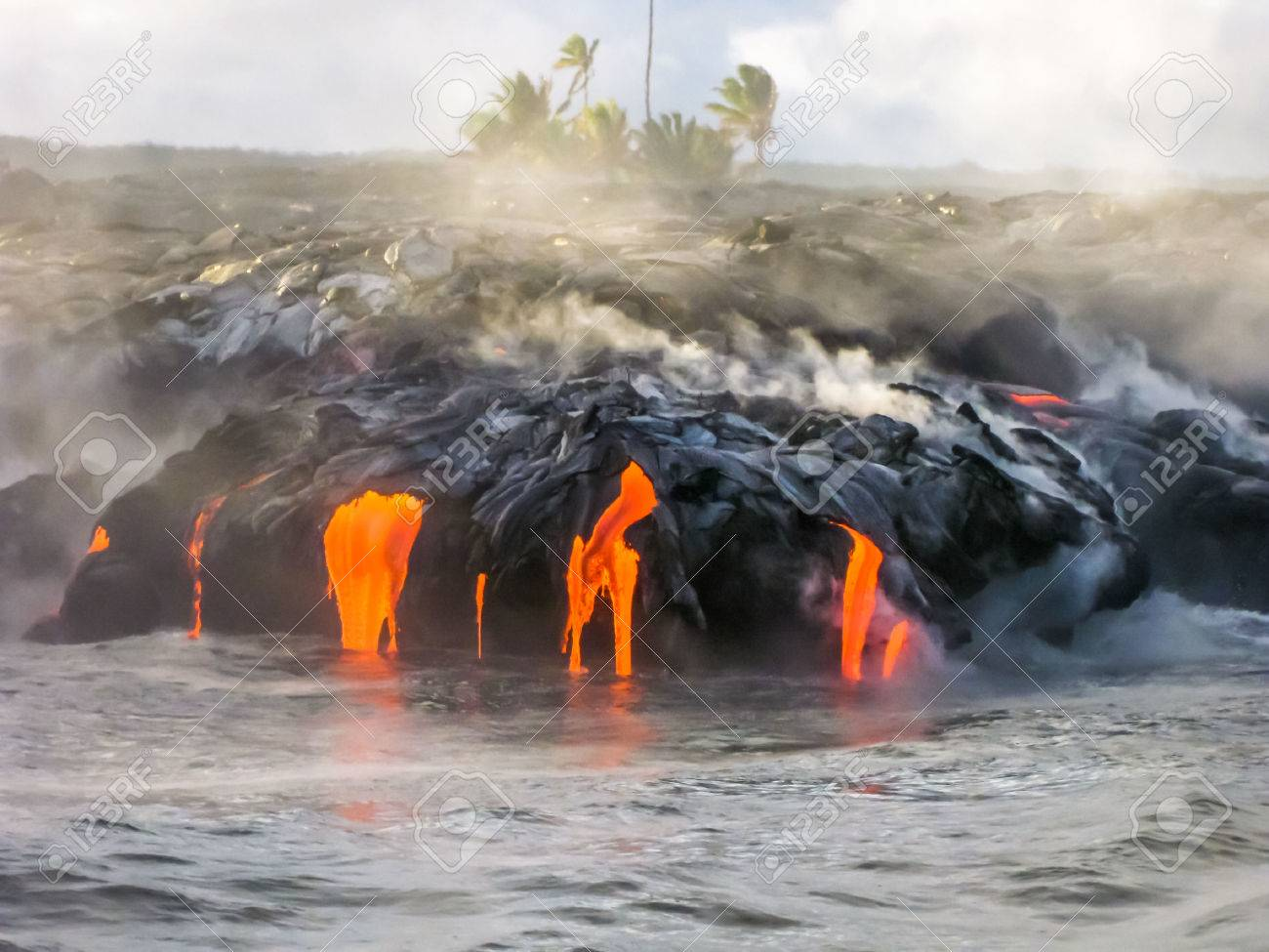 Sea view of Kilauea Volcano in Big Island, Hawaii, United States. A restless volcano that has been in business since 1983. Shot taken at sunset when the lava glows in the dark as jumps into the sea. - 47790757