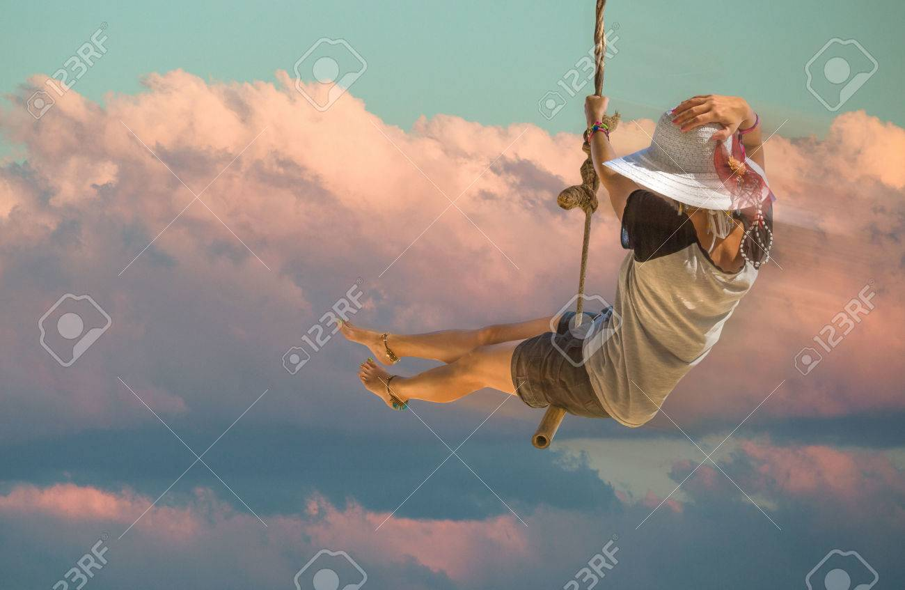 Young woman with shorts, shirt and wide-brimmed hat swinging with sunset sky and cloud background. Freedom concept. Stock Photo - 55356429