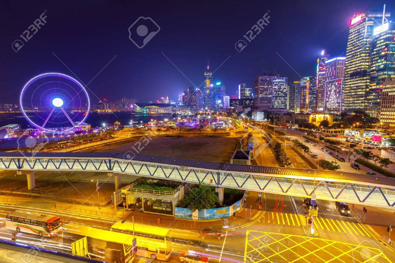 Spectacular aerial view of cityscape in Hong Kong, Central District, with Observation Ferris Wheel at Victoria Harbour illuminated at night. Stock Photo - 68143589