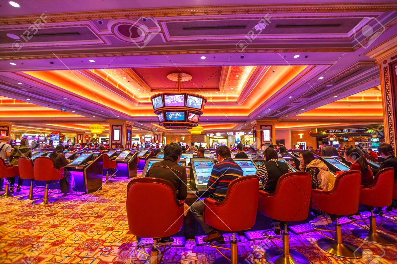 Macau, China - December 9, 2016: people visit The Venetian Casino hall with game machines. The Venetian is the largest casino in the world and the largest single structure hotel building in Asia. - 79909016
