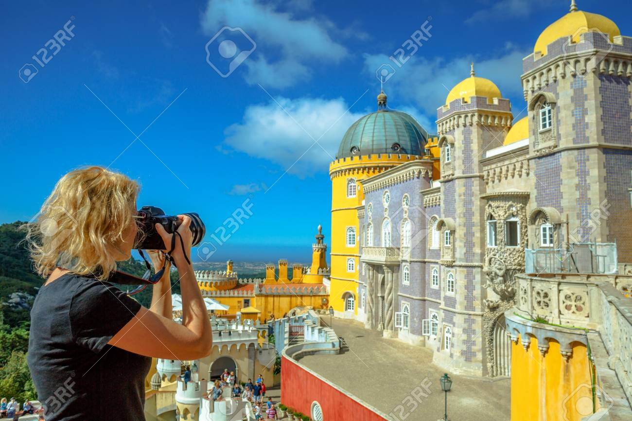 Travel woman photographer takes photos of Pena National Palace. Female photographer with professional camera takes shot of the most visited attraction in Sintra, Portugal. Travel and tourism in Europe - 87115477