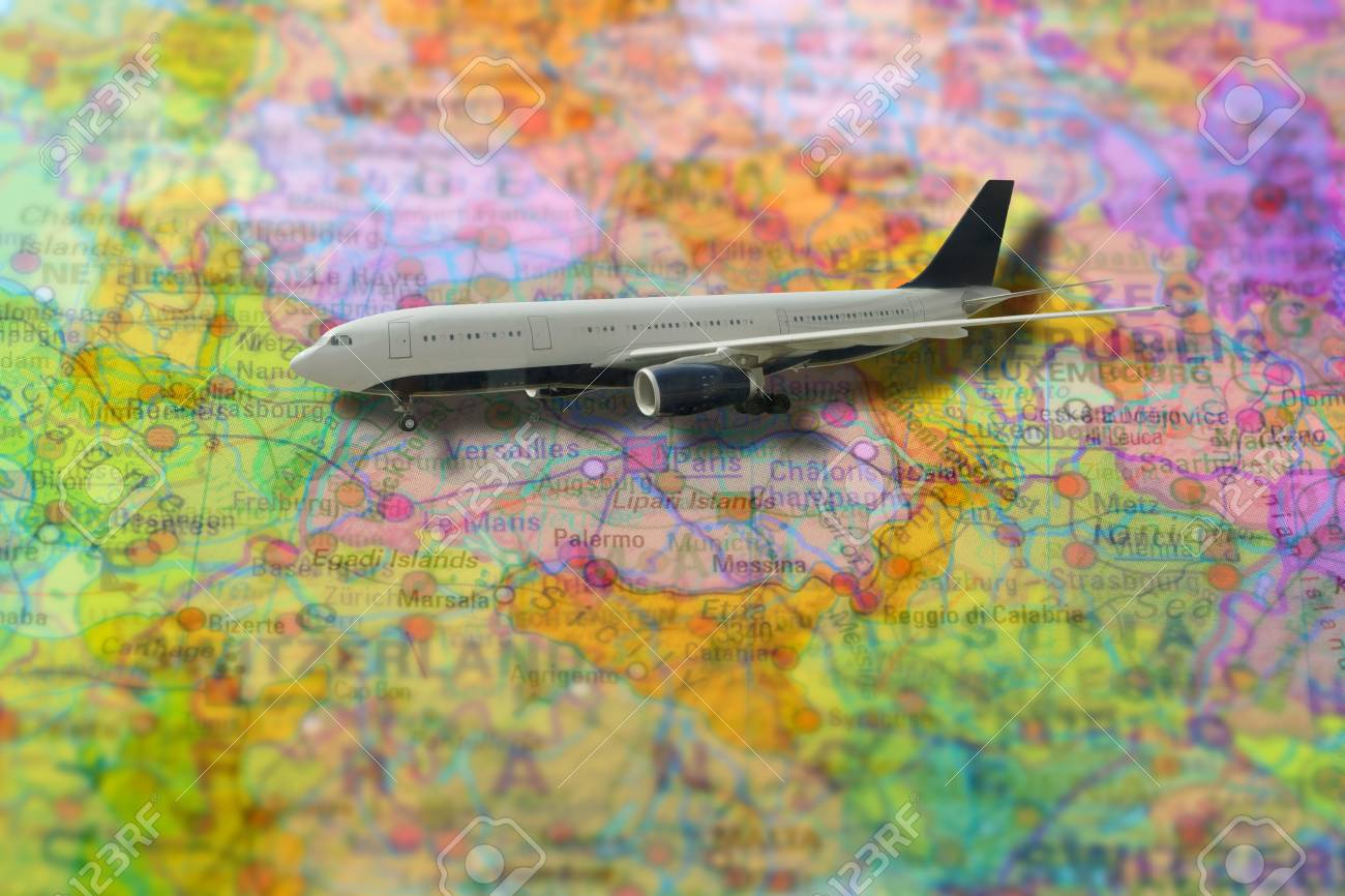 Pinned flight of plane travelling on colorful political map of..