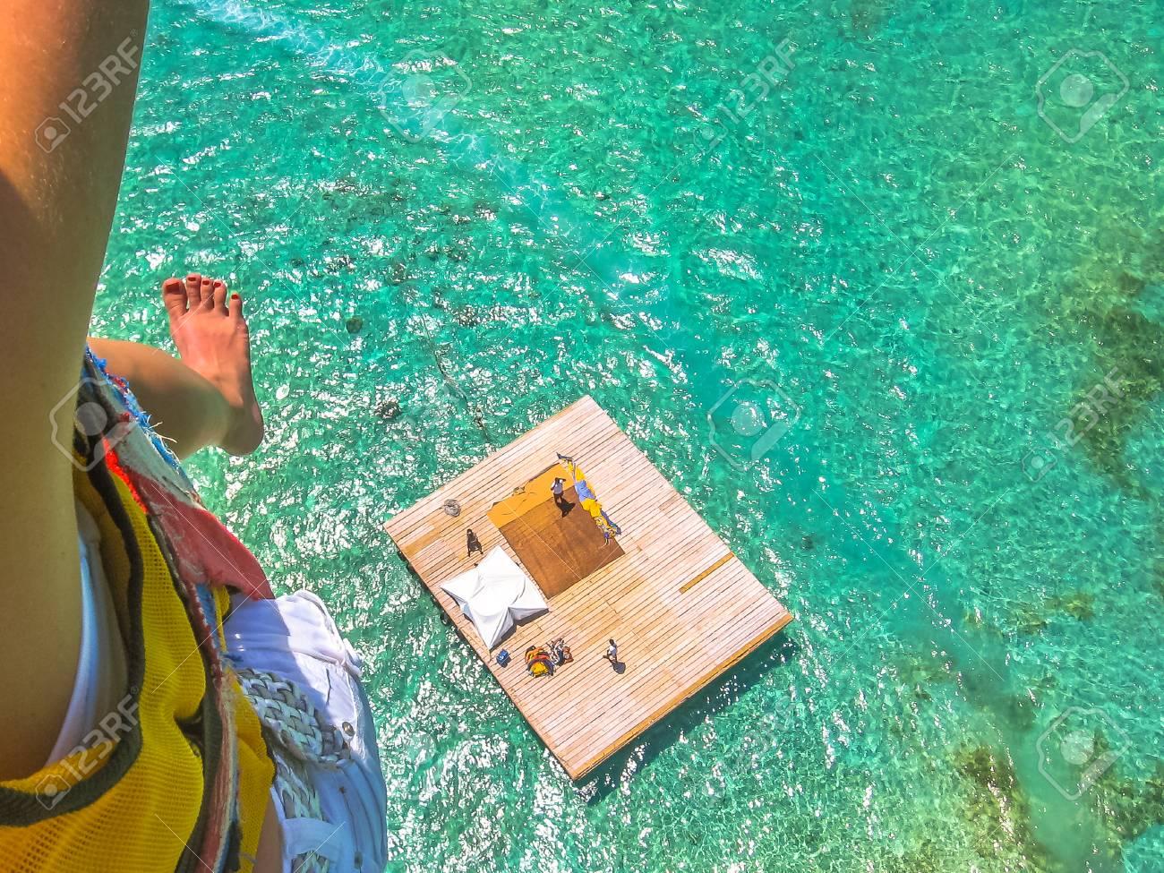 Aerial closeup view of a woman parasailing. Below, the landing platform on the spectacular blue sea of Deer Island, east coast of Mauritius, Indian Ocean. - 102273283