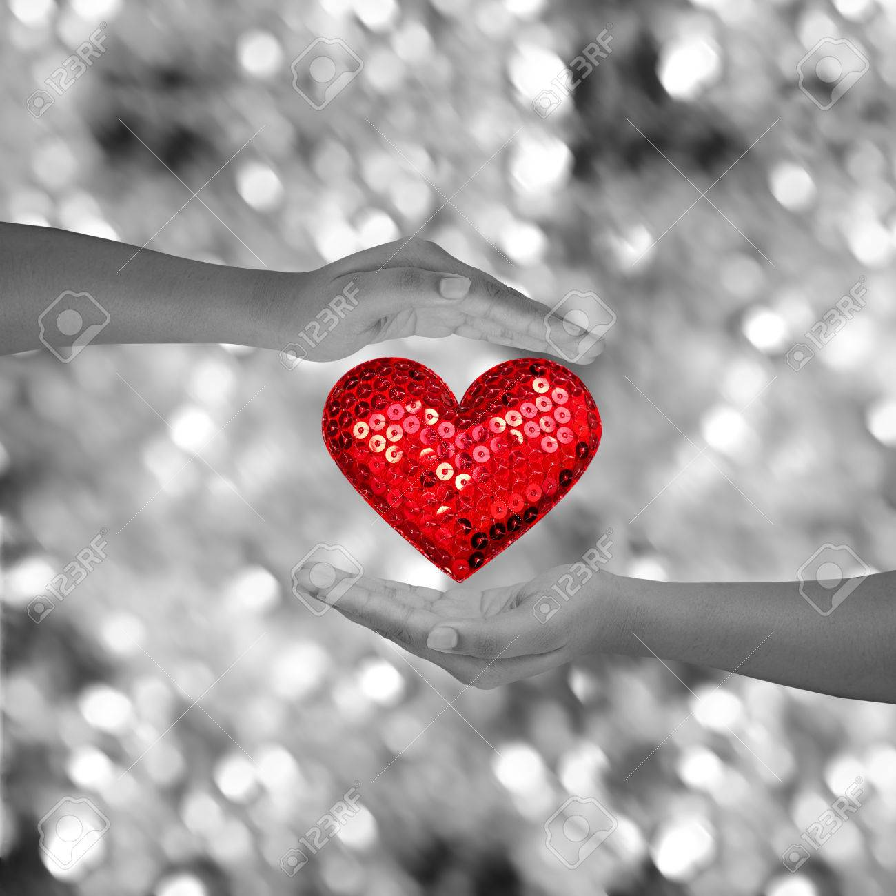 Two hands holding red heart shap on black and white bokeh background