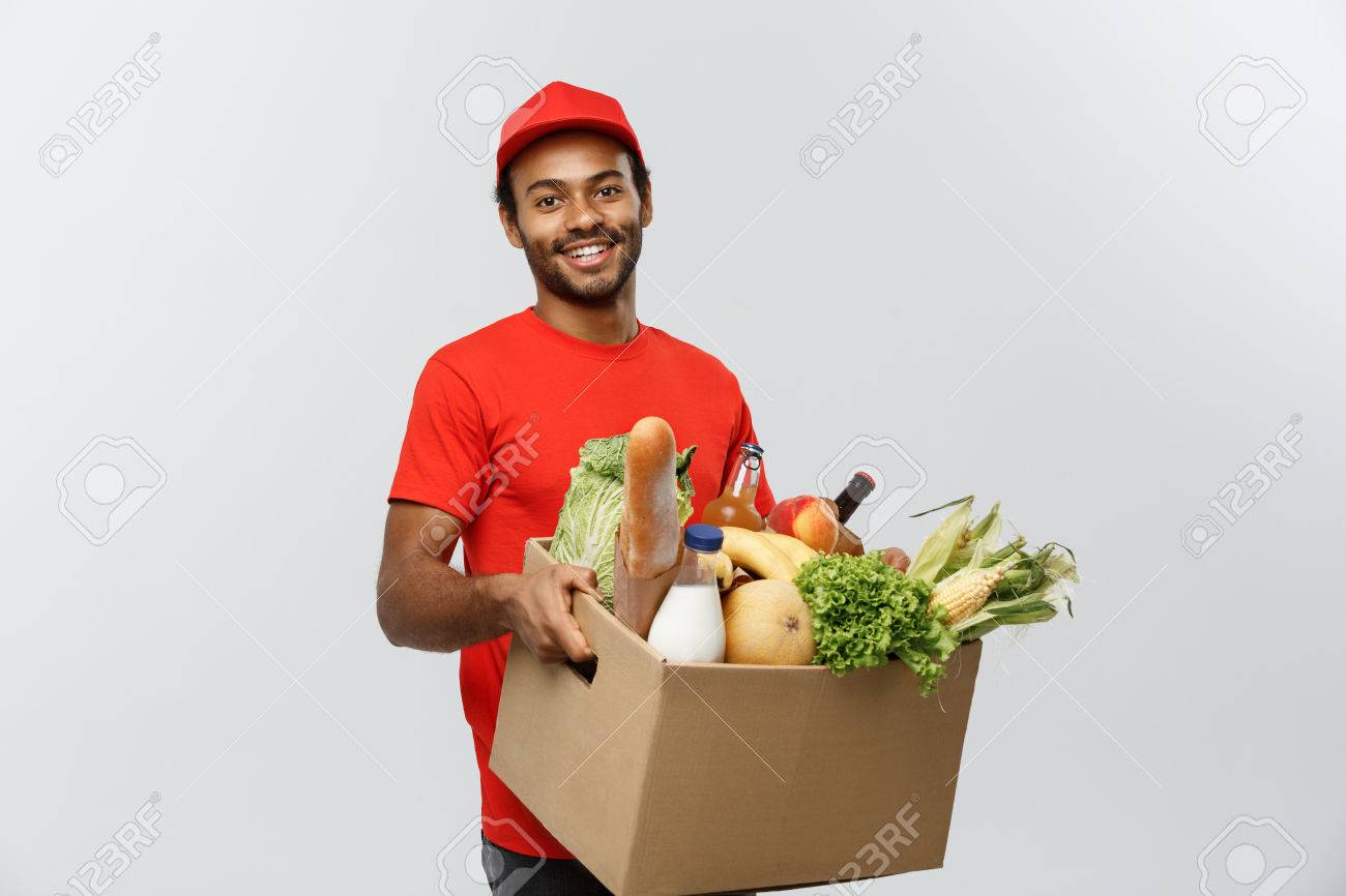 Delivery Concept - Handsome African American delivery man carrying package box of grocery food and drink from store. Isolated on Grey studio Background. Copy Space. - 84925485
