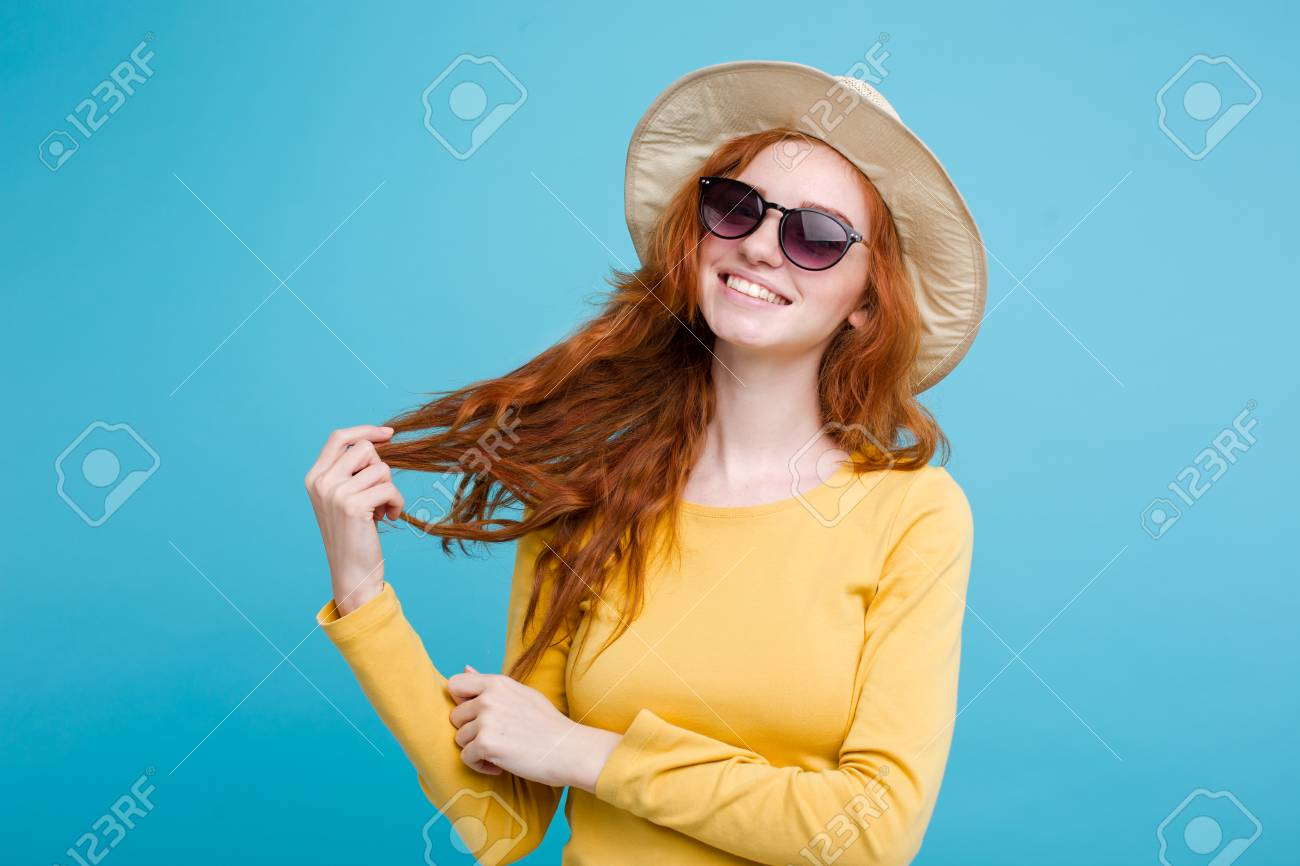 72bfe75bc Stock Photo - Travel concept - Close up Portrait young beautiful attractive  redhair girl wtih trendy hat and sunglass smiling. Blue Pastel Background.