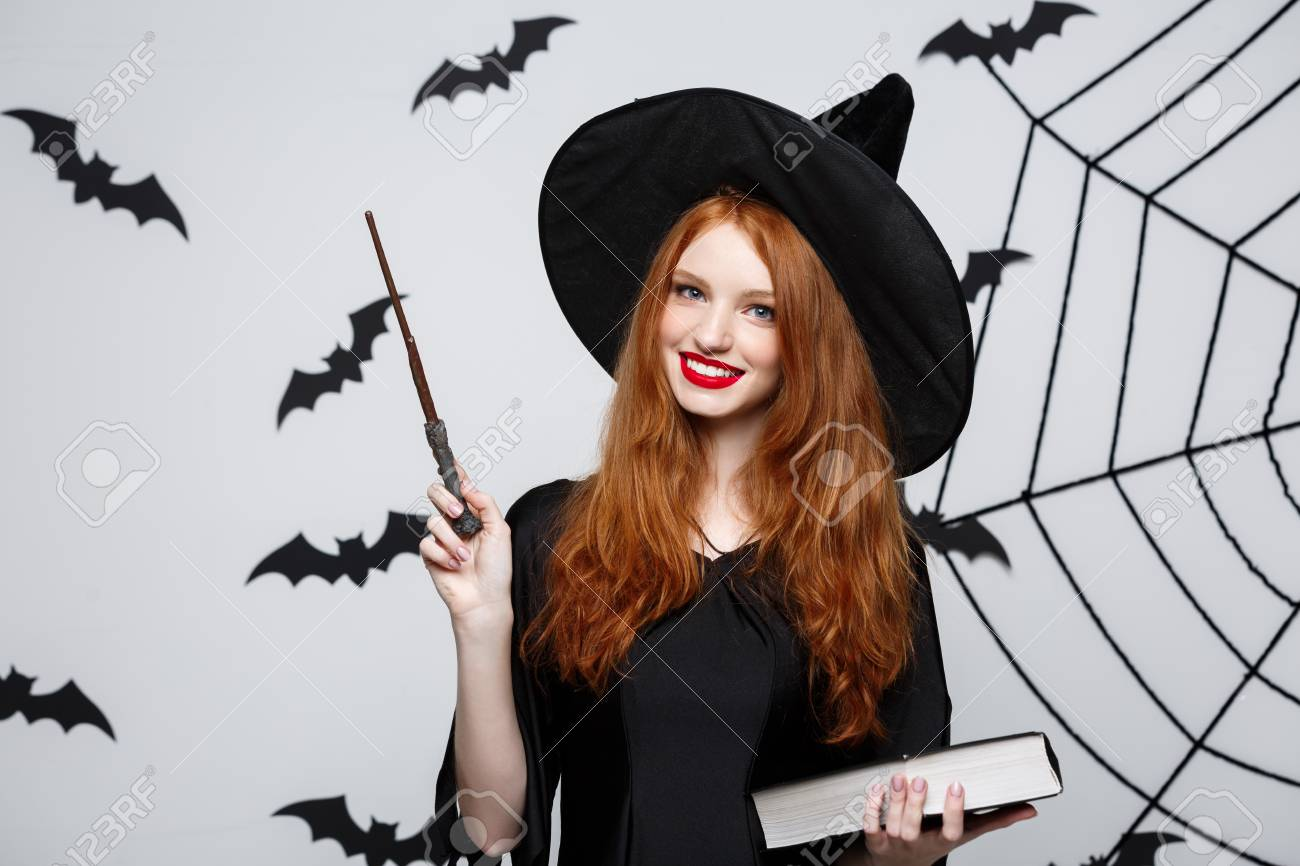 Halloween Concept - Beautiful Witch playing with magic stick on grey background. - 97604922
