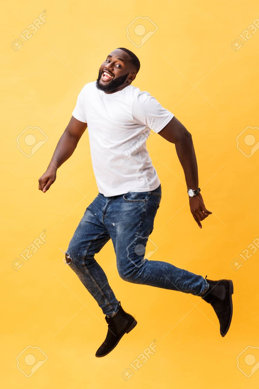 cb2c33688897d Full length of handsome young black man jumping against yellow background.  Stok Fotoğraf - 113688958