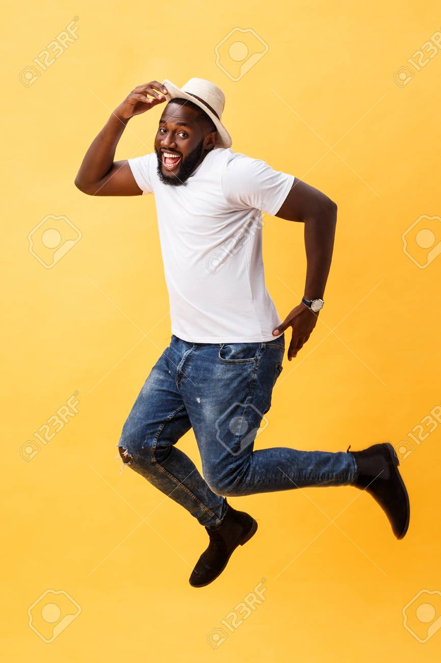 afbe1c4ffa1de Full length of handsome young black man jumping against yellow background.  Stok Fotoğraf - 113688959
