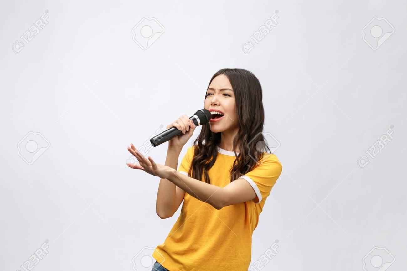 beautiful stylish woman singing karaoke isolated over white background. - 114853439