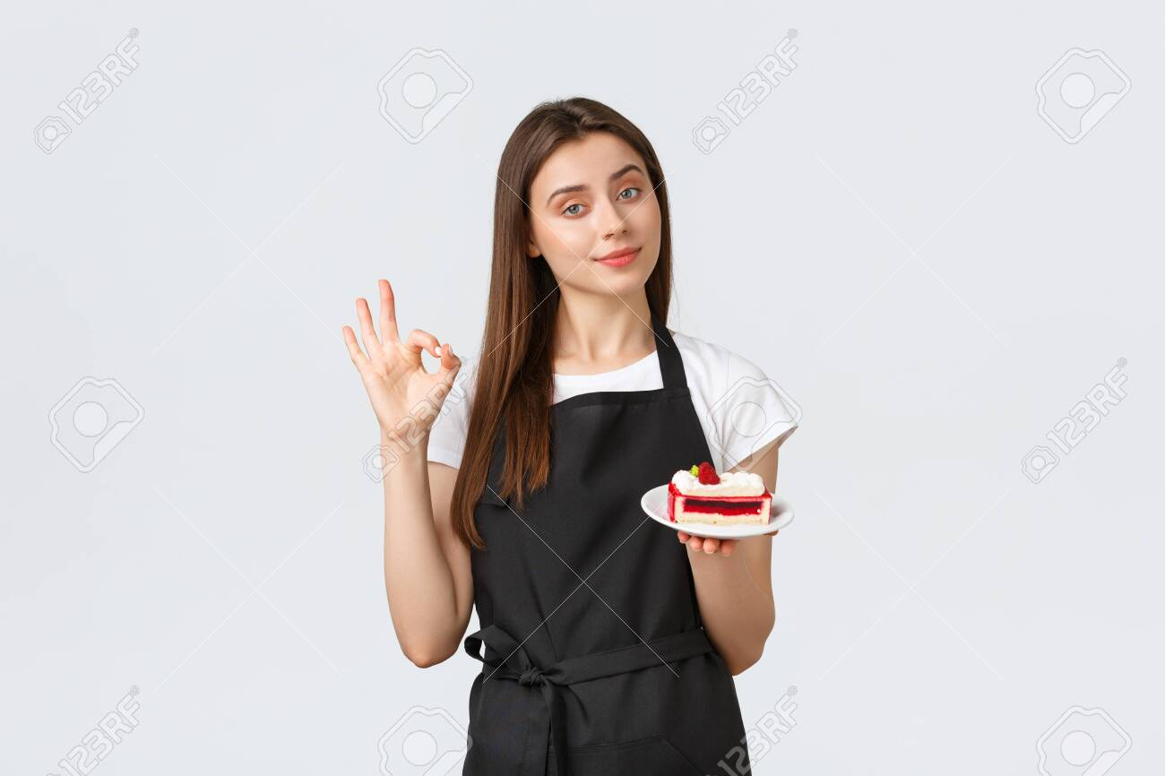 Grocery store employees, small business and coffee shops concept. Cute barista recommend delicious cake, showing okay gesture, guarantee that desserts in cafe delicious, white background - 150060877