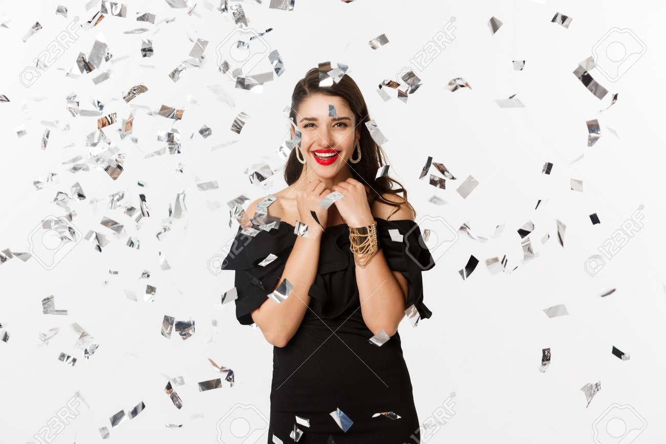 Happy woman celebrating winter holidays, smiling cheerful, partying on New Year with confetti, standing over white background - 159590099