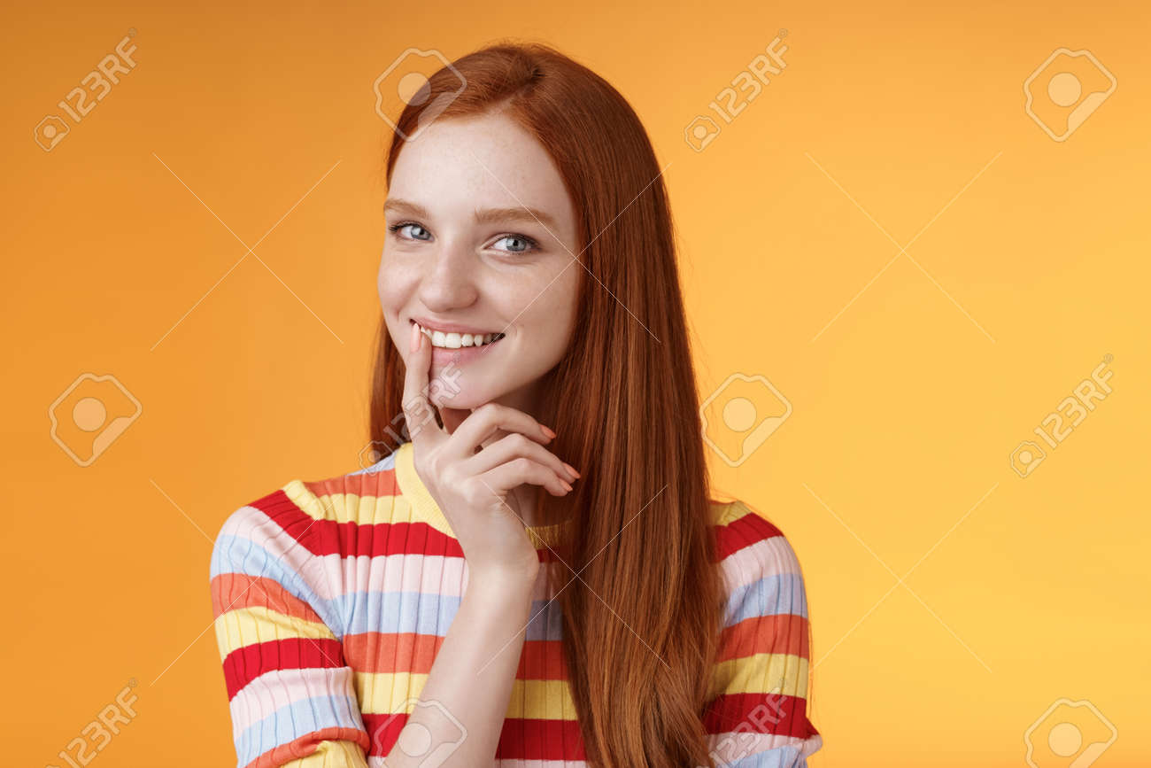 Curious devious redhead young 20s girlfriend have excellent idea smirking tricky touch lip flirty mysteriously glancing camera have plans preparing interesting surprise, standing orange background - 166528712