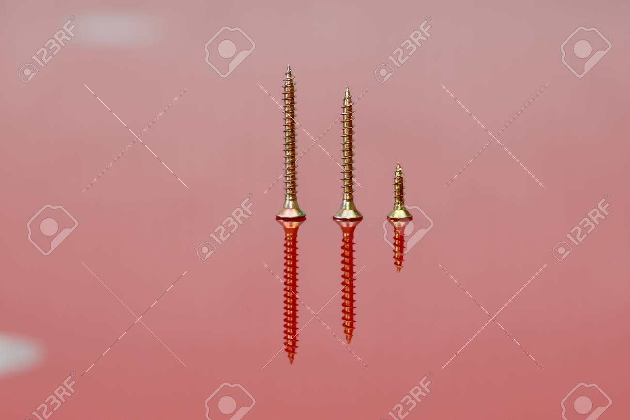 Some drywall screws of different sizes on a red reflecting surface