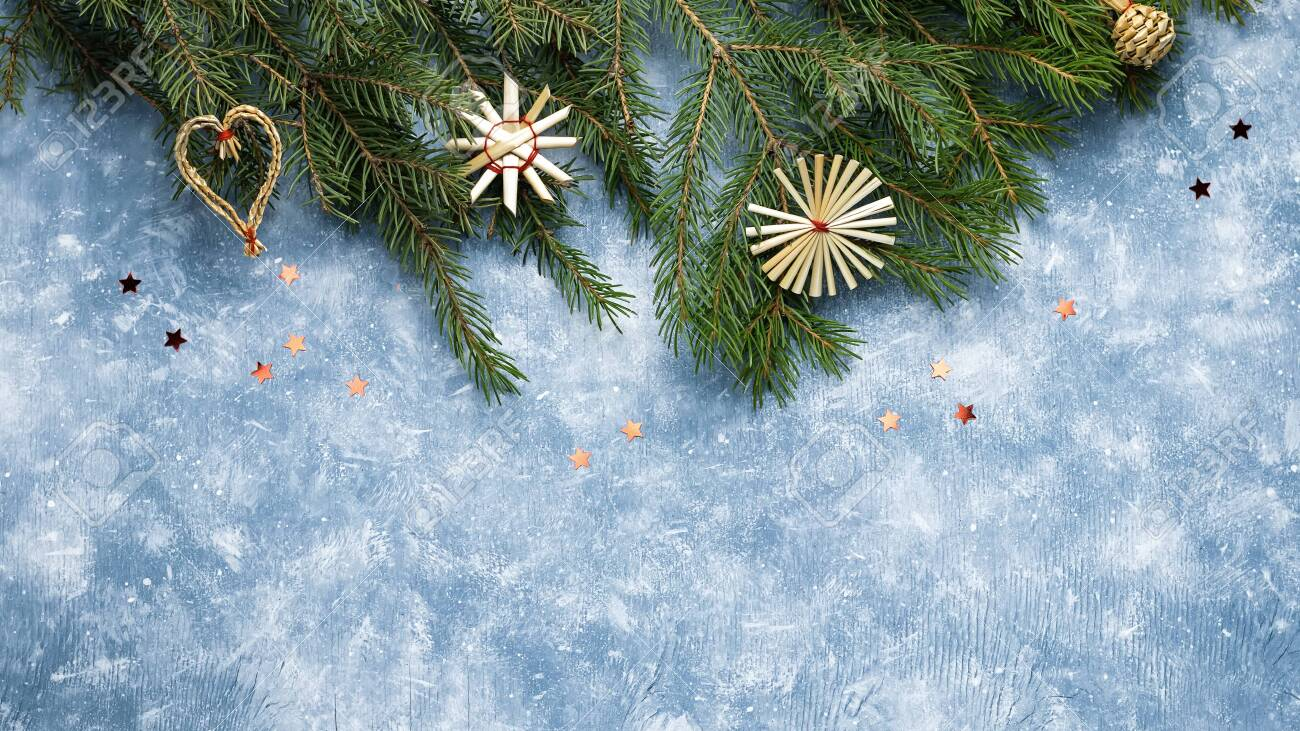 Christmas card with fir tree branches, red ribbons and decorations, wooden ornaments, confetti. Copy space, top view - 129197317