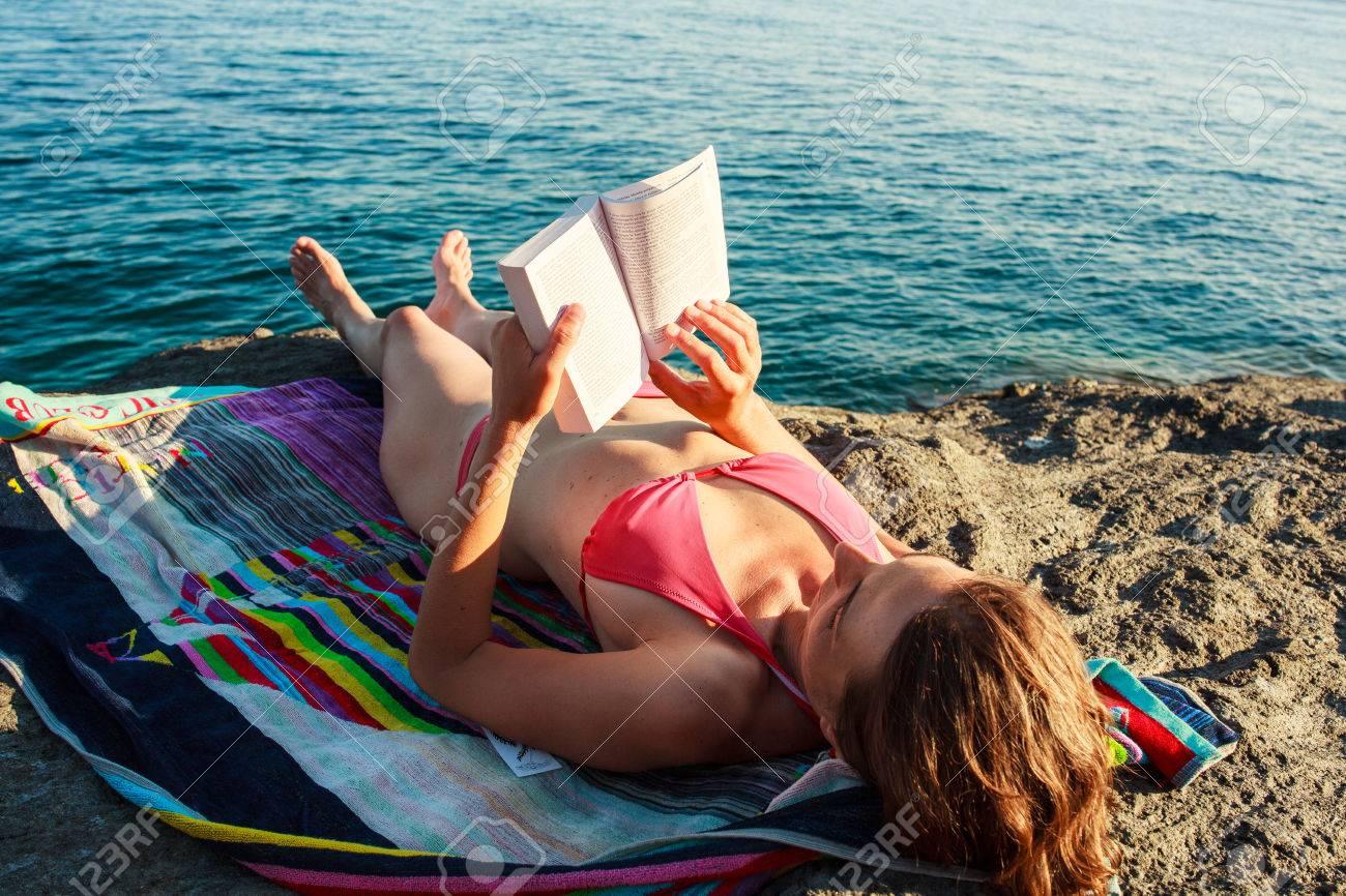 Girl Reading book in the beach, Pantelleria Stock Photo - 22485780